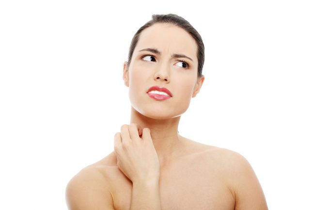 Beauty girl with perfect skin scratching her neck