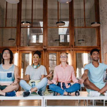 International students meditating on the desks in library, relaxing before exams. University friends doing yoga on the table with eyes closed..