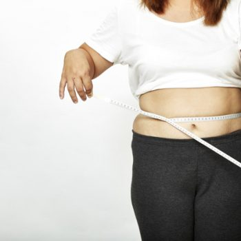 Fat young woman asian with measure tape on white background.