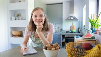 Happy woman leaning on counter with fruits
