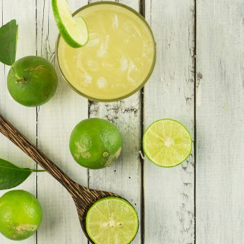 Top view of lime juice with ice on white wood