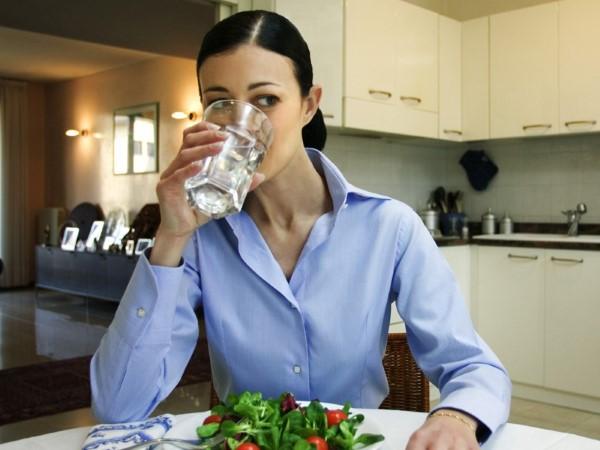 Mulher bebendo água pois, hidratação é importante em como aumentar a massa muscular