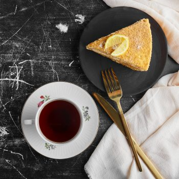 A slice of honey cake with lemon with a cup of tea