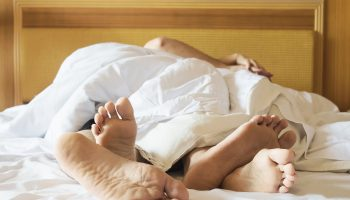 Couple on white bed in hotel room focus at feet