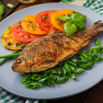 Fried fish carp and fresh vegetable salad on wooden background.